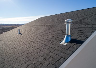 A shingle roof with the backyard in the distance.