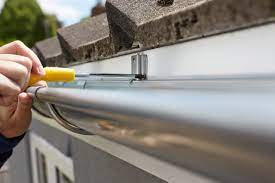 A contractor working on repairing gutters.