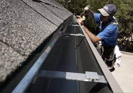 A contractor installing new gutters.