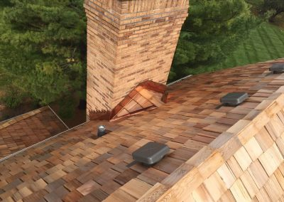 A beautiful cedar shake roof with a brick chimney.