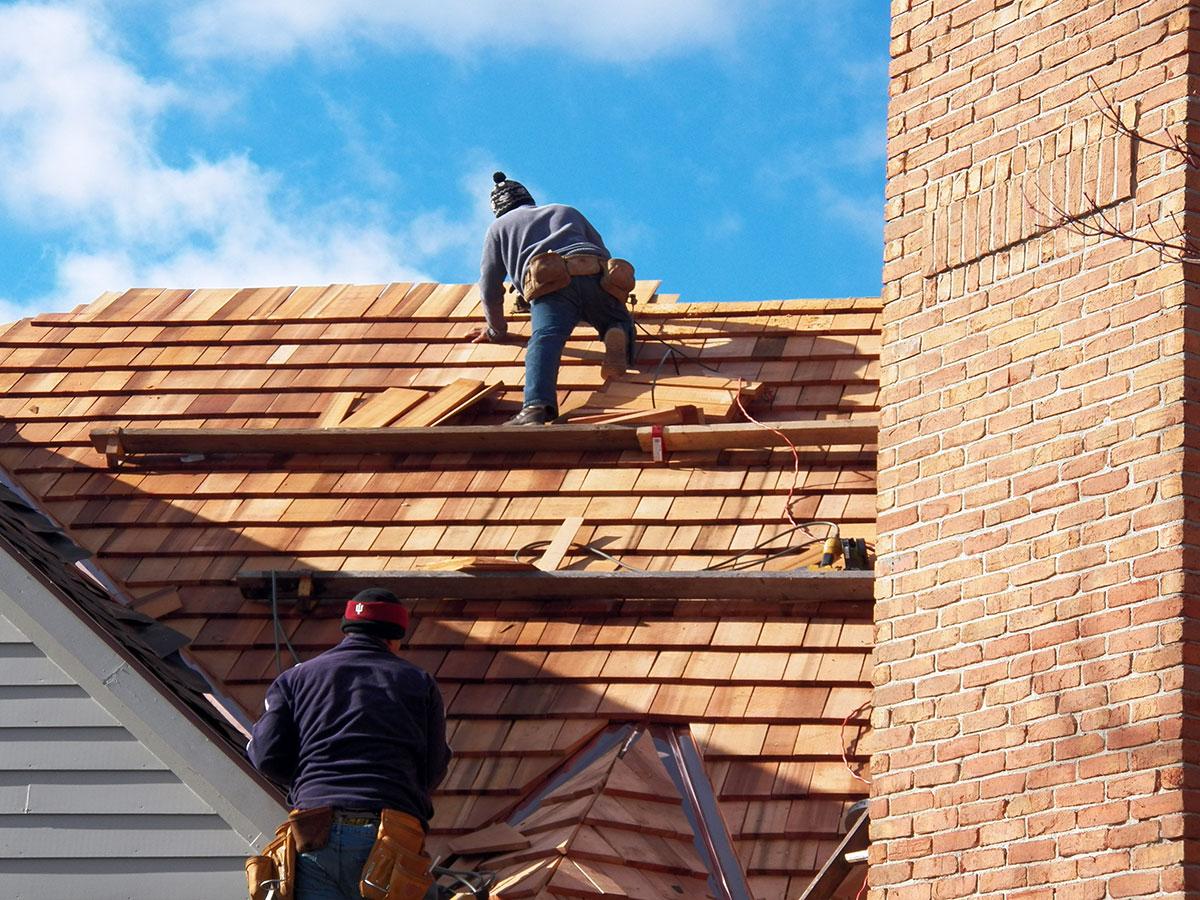 Roofing contractors installing a cedar shake roof.