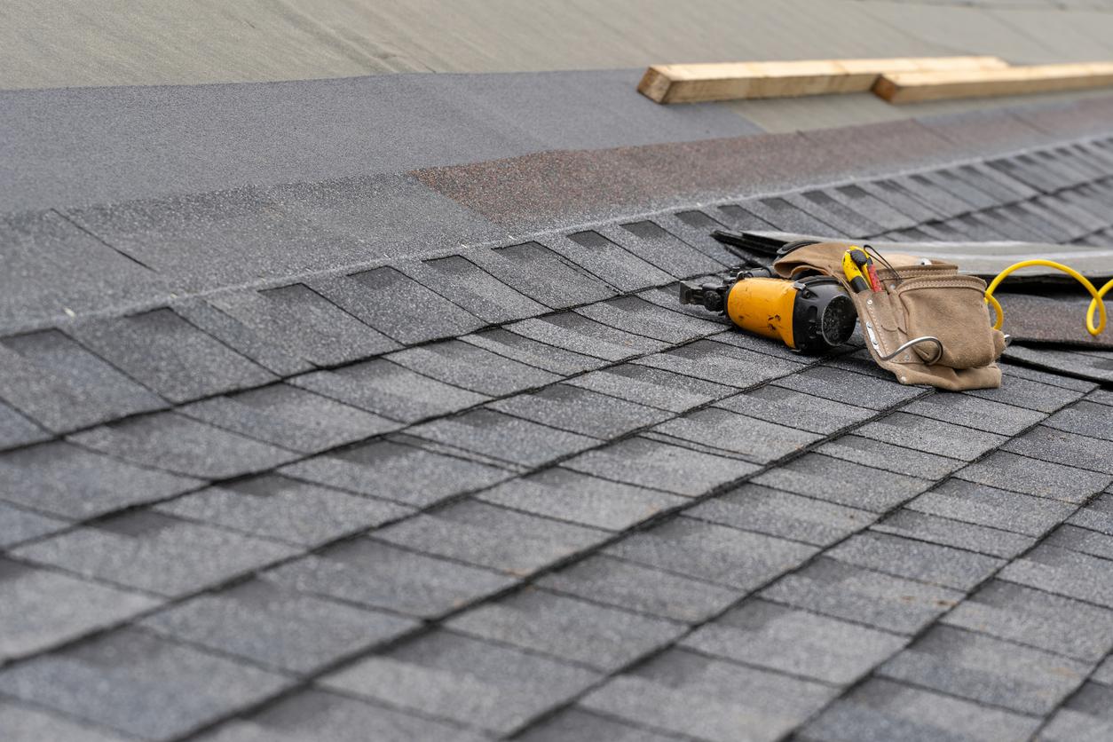 A nail gun sitting on a composite roof during a repair.