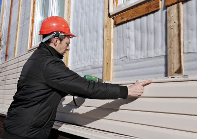 A contractor installing new siding.