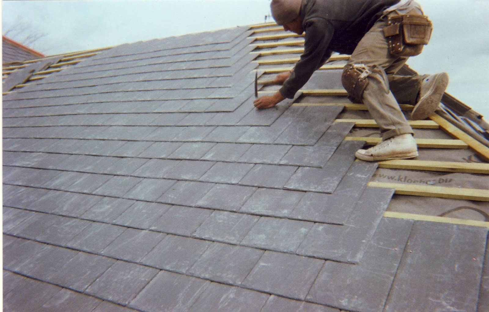 A roofing contractor working on a slate roof.