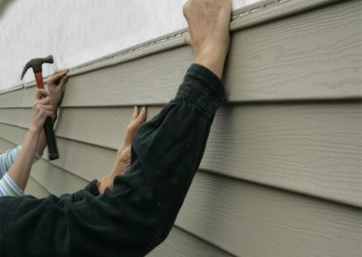 Two of our contractors working on a repair to vinyl siding.